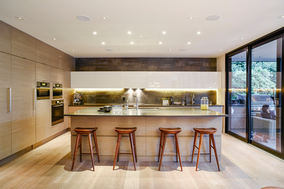 Trendy l-shaped light wood floor kitchen photo in Vancouver with an undermount sink, flat-panel cabinets, light wood cabinets, quartz countertops, porcelain backsplash, stainless steel appliances and an island