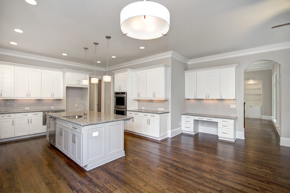 Large transitional u-shaped dark wood floor eat-in kitchen photo in Charlotte with an undermount sink, shaker cabinets, white cabinets, granite countertops, gray backsplash, ceramic backsplash, stainless steel appliances and an island