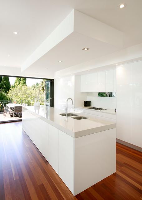 Idéer för ett modernt kök, med en undermonterad diskho, släta luckor, vita skåp, bänkskiva i kvarts, vitt stänkskydd, mellanmörkt trägolv och en köksö