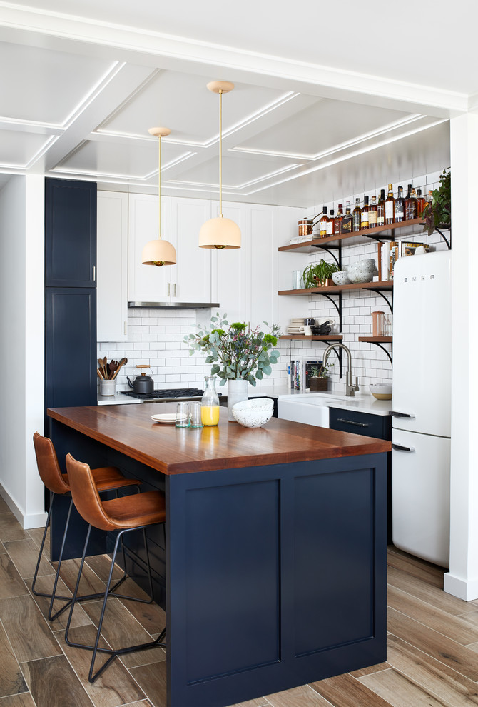 Example of a small eclectic l-shaped porcelain tile and brown floor open concept kitchen design in DC Metro with a farmhouse sink, shaker cabinets, blue cabinets, quartz countertops, white backsplash, ceramic backsplash, white appliances and an island