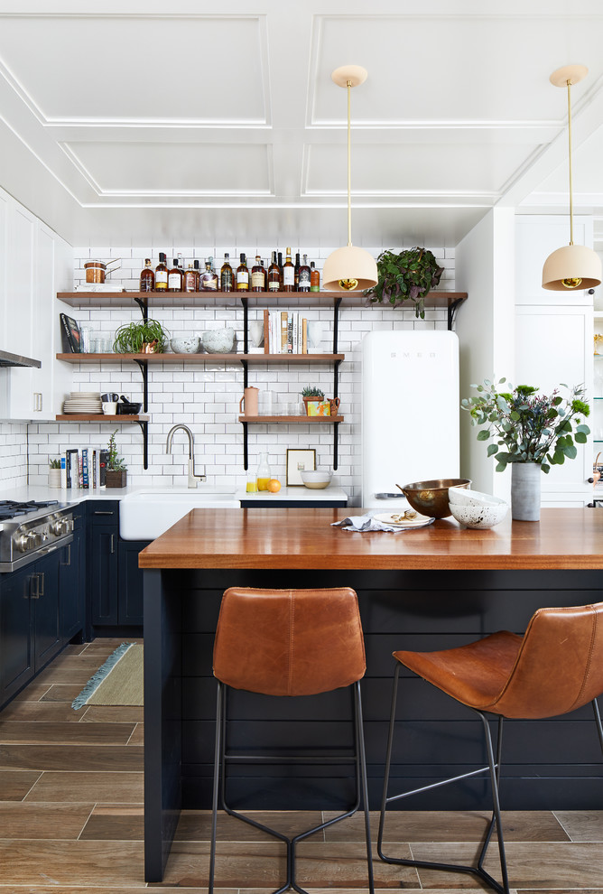 Small trendy l-shaped porcelain tile and brown floor open concept kitchen photo in DC Metro with a farmhouse sink, shaker cabinets, blue cabinets, wood countertops, white backsplash, ceramic backsplash, an island, white appliances and brown countertops