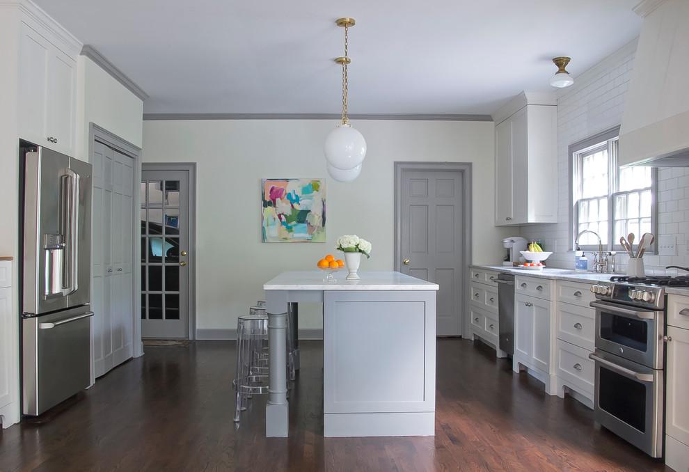 Kitchen - transitional galley dark wood floor kitchen idea in Atlanta with an undermount sink, shaker cabinets, white cabinets, white backsplash, stainless steel appliances and an island