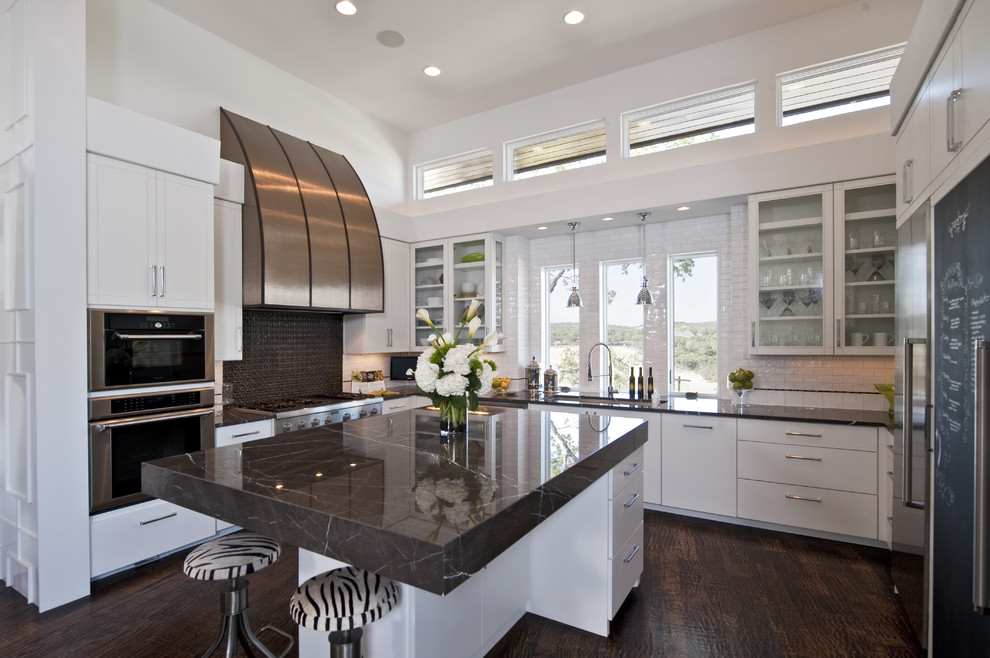 Kitchen - contemporary u-shaped kitchen idea in Austin with glass-front cabinets, stainless steel appliances, white cabinets, white backsplash and subway tile backsplash