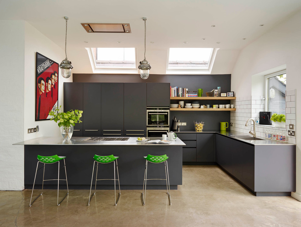 Large trendy concrete floor open concept kitchen photo in London with flat-panel cabinets, gray cabinets, stainless steel countertops, stainless steel appliances, a peninsula and an integrated sink