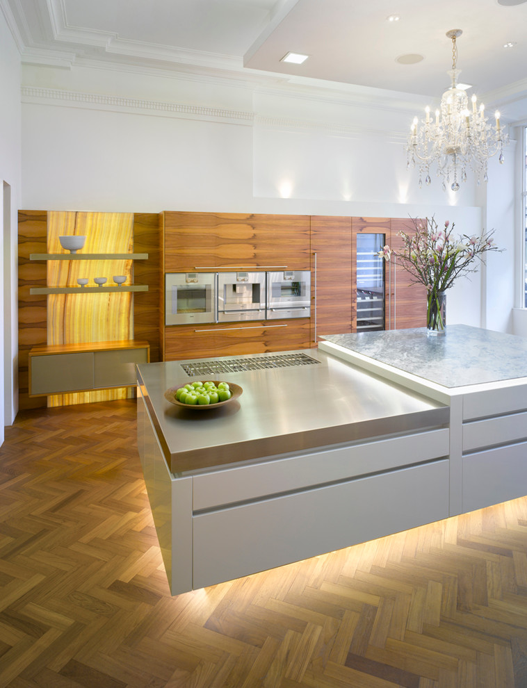 Inspiration for a large contemporary medium tone wood floor open concept kitchen remodel in London with flat-panel cabinets, medium tone wood cabinets, quartzite countertops, stainless steel appliances and an island