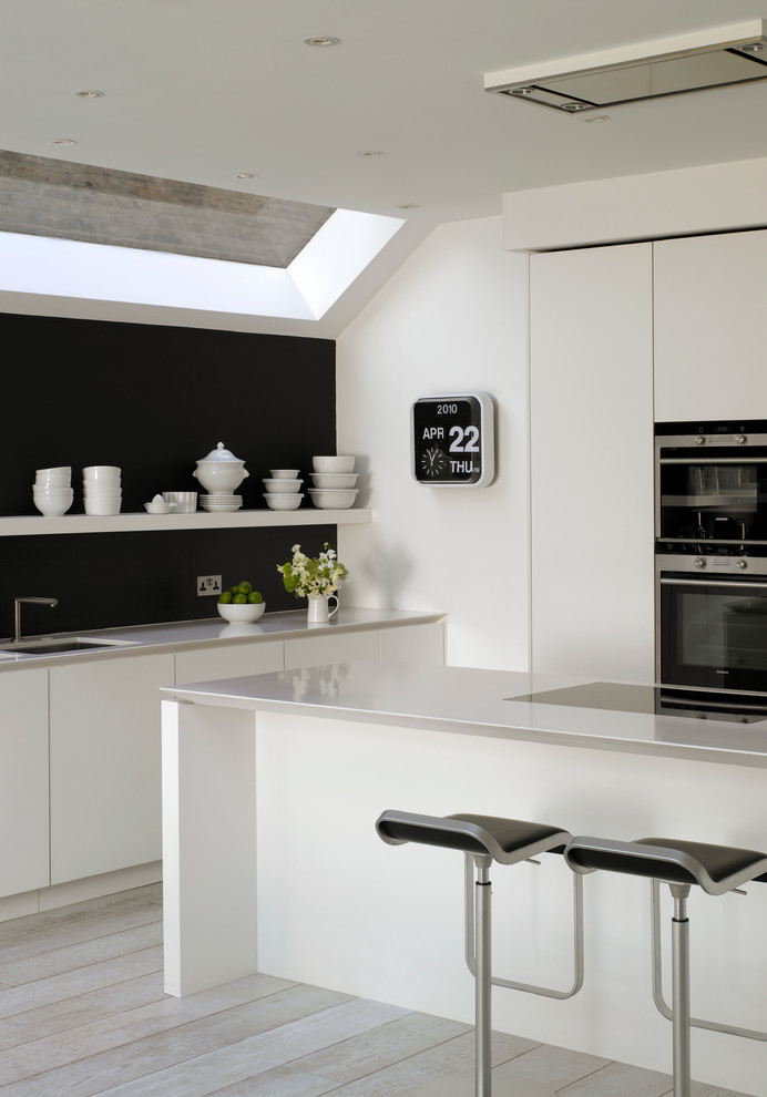Example of a large trendy kitchen design in London with flat-panel cabinets, white cabinets, quartz countertops and an undermount sink