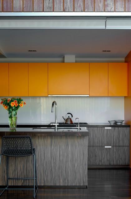 Modern kitchen in Sydney with flat-panel cabinets, orange cabinets and grey splashback.