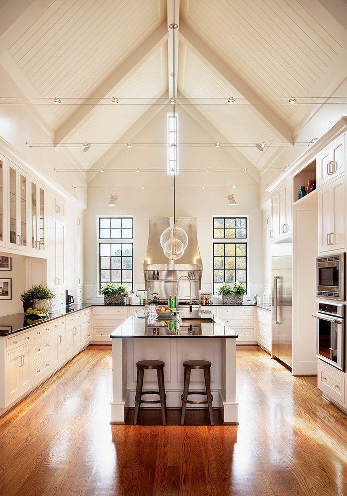 Huge elegant u-shaped medium tone wood floor kitchen photo in Raleigh with shaker cabinets, white cabinets, stainless steel appliances, an undermount sink, granite countertops, an island and black countertops
