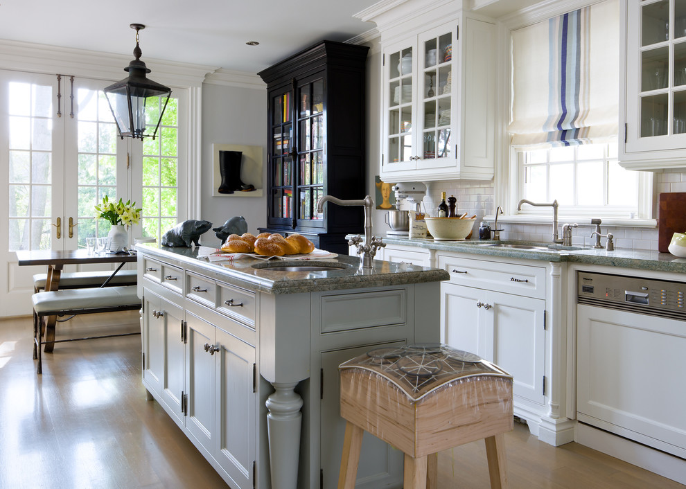 Example of a classic eat-in kitchen design in Toronto with an undermount sink, recessed-panel cabinets, white cabinets, white backsplash, subway tile backsplash and paneled appliances