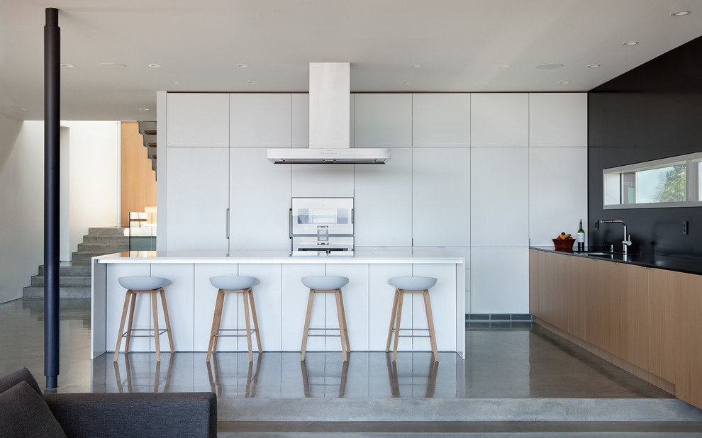Minimalist l-shaped concrete floor open concept kitchen photo in Vancouver with an undermount sink, flat-panel cabinets, white cabinets and black backsplash