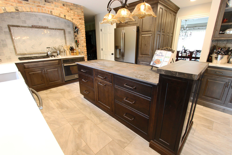 Inspiration for a large transitional l-shaped kitchen pantry remodel in Cleveland with a farmhouse sink, raised-panel cabinets, green cabinets, quartz countertops, white backsplash, stone tile backsplash, stainless steel appliances, an island and white countertops
