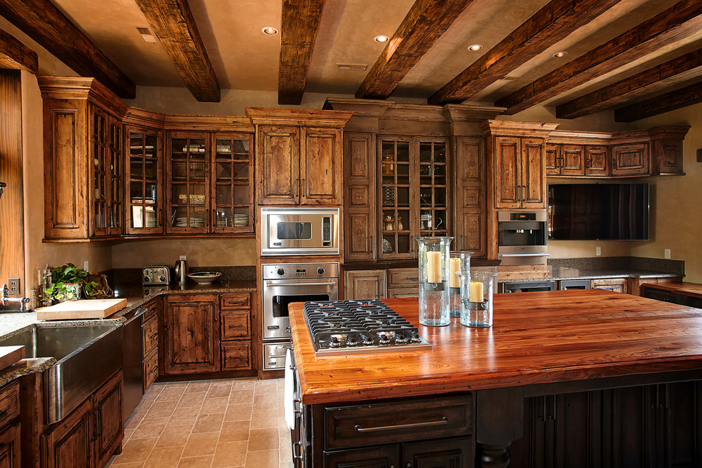 Kitchen pantry - large rustic l-shaped kitchen pantry idea in Kansas City with a farmhouse sink, medium tone wood cabinets, stainless steel appliances and an island