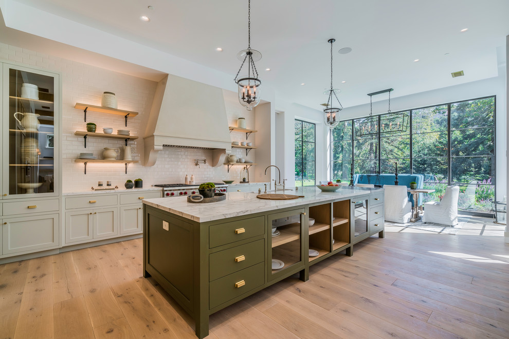 Kitchen - transitional light wood floor kitchen idea in Los Angeles with white backsplash, subway tile backsplash, stainless steel appliances and an island