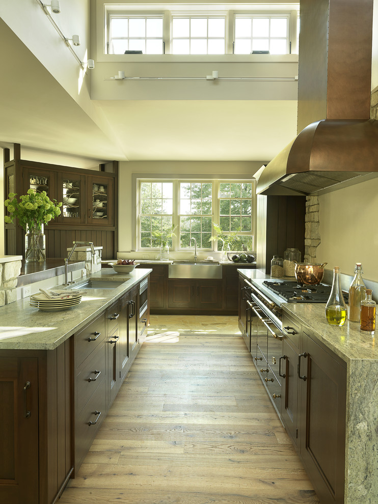 Trendy kitchen photo in St Louis with a farmhouse sink, granite countertops, recessed-panel cabinets and dark wood cabinets