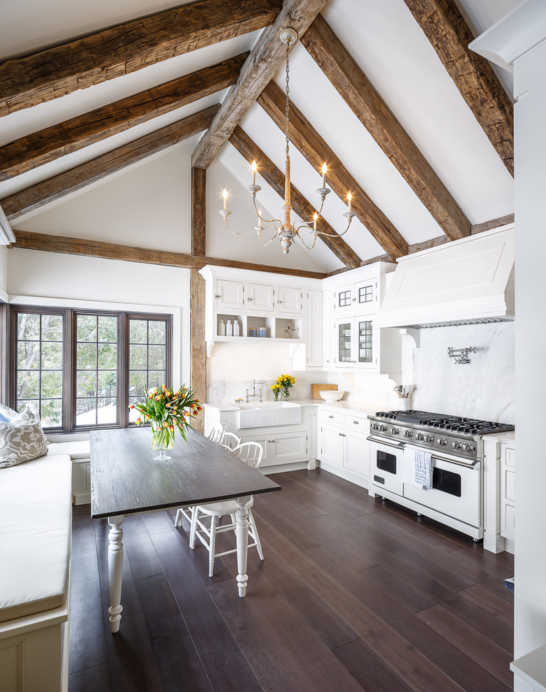 Mid-sized farmhouse l-shaped dark wood floor and brown floor eat-in kitchen photo in Ottawa with white cabinets, white backsplash, white appliances, no island, a farmhouse sink, stone slab backsplash, recessed-panel cabinets and quartz countertops