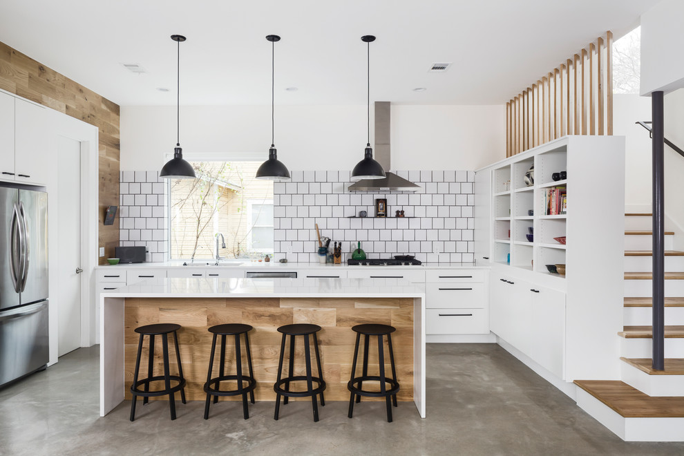 Inspiration for a mid-sized scandinavian concrete floor and gray floor open concept kitchen remodel in Austin with flat-panel cabinets, white cabinets, white backsplash, ceramic backsplash, stainless steel appliances, an island and white countertops