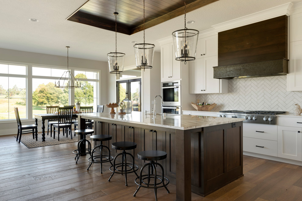 Inspiration for a farmhouse dark wood floor and brown floor eat-in kitchen remodel in Minneapolis with an undermount sink, shaker cabinets, white cabinets, white backsplash, stainless steel appliances, an island and white countertops