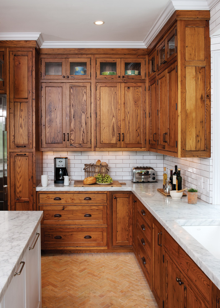 Inspiration for a rustic l-shaped brick floor kitchen remodel in Burlington with an undermount sink, recessed-panel cabinets, medium tone wood cabinets, granite countertops, white backsplash and subway tile backsplash