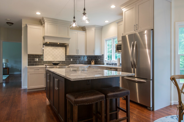 Inspiration for a mid-sized transitional l-shaped medium tone wood floor eat-in kitchen remodel in Bridgeport with an undermount sink, recessed-panel cabinets, gray cabinets, granite countertops, black backsplash, ceramic backsplash, stainless steel appliances and an island