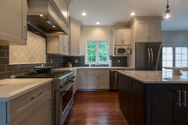 Mid-sized transitional l-shaped medium tone wood floor eat-in kitchen photo in Bridgeport with an undermount sink, recessed-panel cabinets, gray cabinets, granite countertops, black backsplash, ceramic backsplash, stainless steel appliances and an island