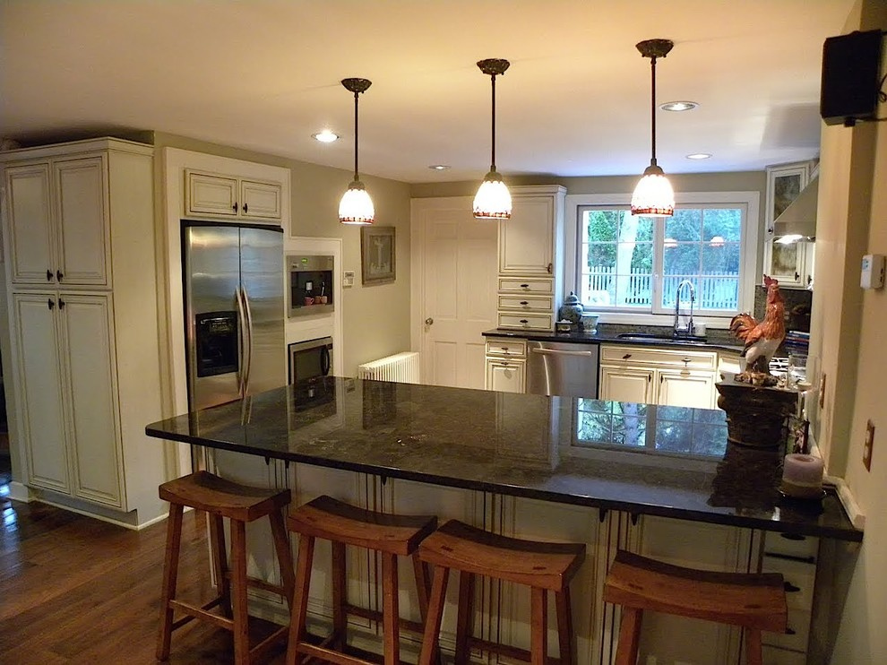 Elegant u-shaped medium tone wood floor eat-in kitchen photo in New York with a double-bowl sink, beaded inset cabinets, white cabinets, granite countertops, multicolored backsplash, mosaic tile backsplash, stainless steel appliances and no island