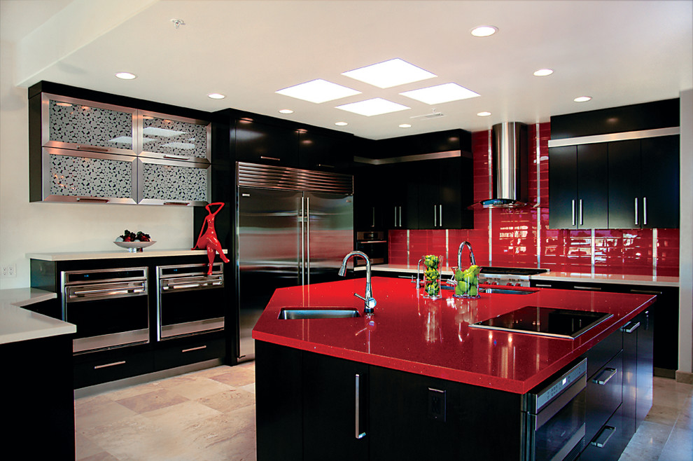 Trendy kitchen photo in Phoenix with stainless steel appliances, an undermount sink, flat-panel cabinets, black cabinets, quartz countertops, red backsplash and red countertops