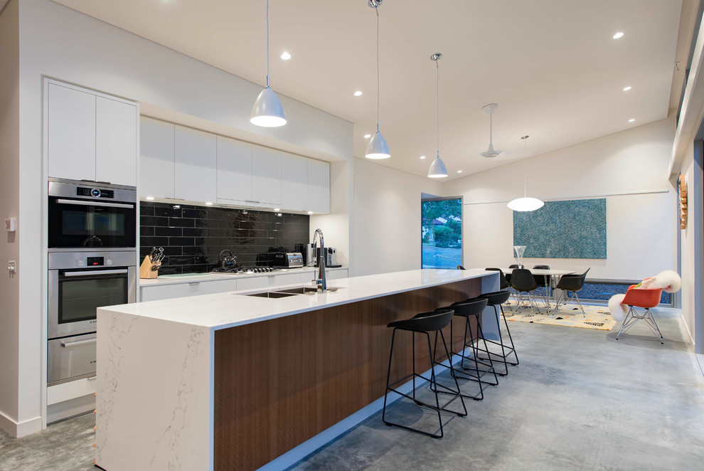 Example of a trendy galley concrete floor eat-in kitchen design in Canberra - Queanbeyan with a double-bowl sink, flat-panel cabinets, white cabinets, black backsplash, stainless steel appliances and an island