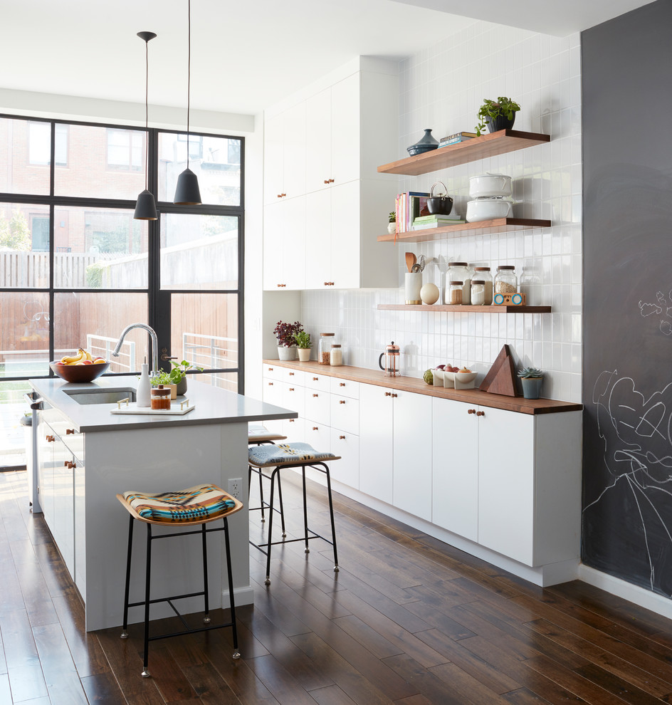 Photo of a contemporary galley kitchen in New York with an undermount sink, flat-panel cabinets, white cabinets, wood benchtops, white splashback, dark hardwood floors, with island, brown floor and brown benchtop.