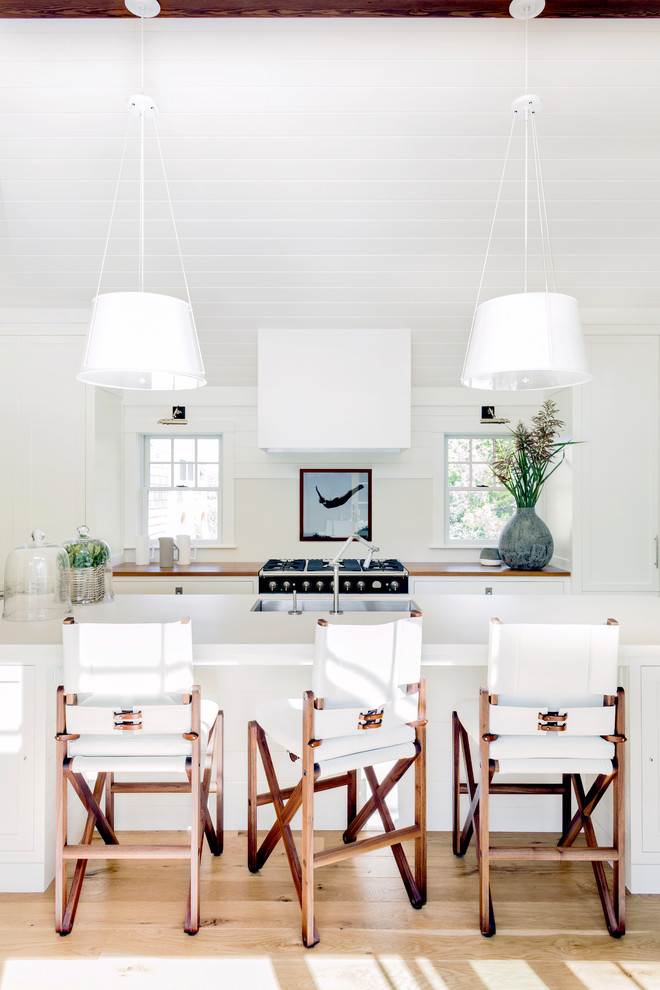 Inspiration for a transitional light wood floor open concept kitchen remodel in Boston with an undermount sink, shaker cabinets, white cabinets, wood countertops, white backsplash, black appliances and an island
