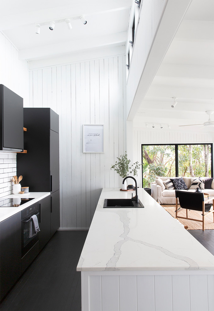 Example of a beach style galley painted wood floor and black floor open concept kitchen design in Sunshine Coast with a drop-in sink, flat-panel cabinets, black cabinets, white backsplash, black appliances, a peninsula and white countertops