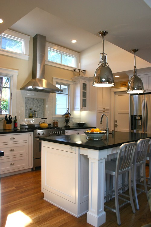 Kitchen with shiny silver industrial light fixtures above a black kitchen island table