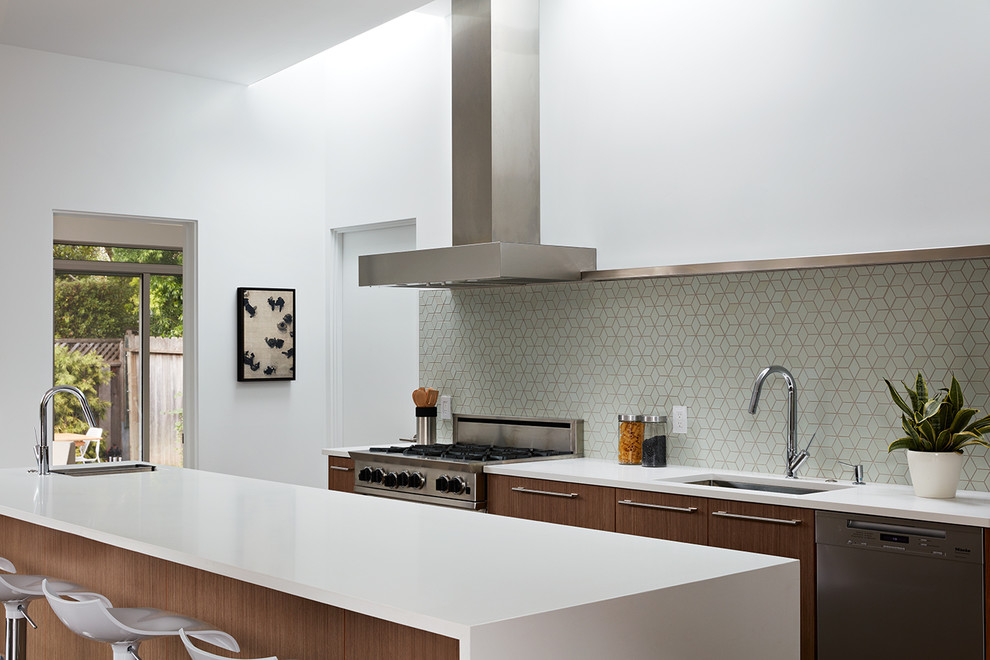 Inspiration for a mid-sized 1960s galley porcelain floor and brown floor eat-in kitchen remodel in San Francisco with an undermount sink, flat-panel cabinets, dark wood cabinets, green backsplash, stainless steel appliances and an island