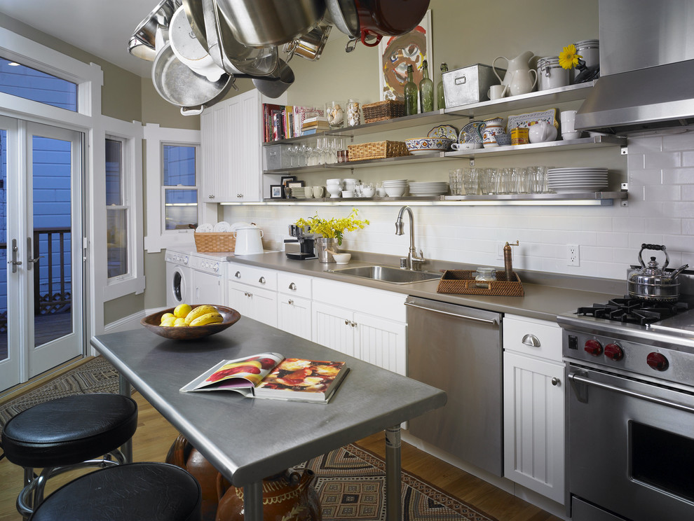 Example of a mid-sized eclectic galley light wood floor eat-in kitchen design in San Francisco with subway tile backsplash, a drop-in sink, beaded inset cabinets, white cabinets, white backsplash, stainless steel appliances, an island and solid surface countertops