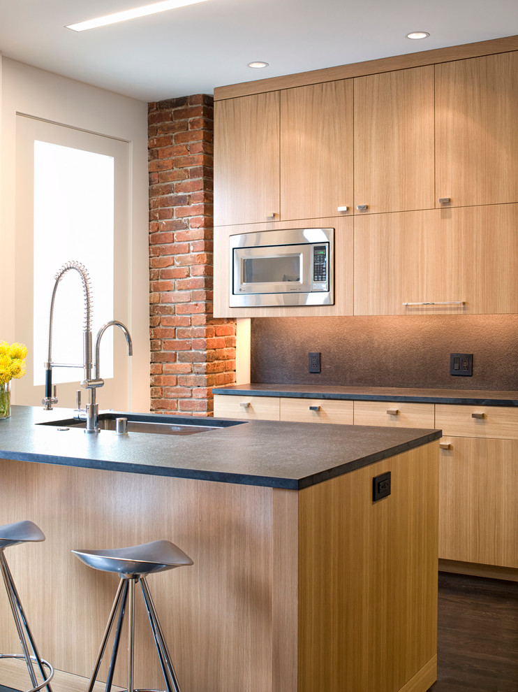 Example of a mid-sized urban galley dark wood floor and brown floor eat-in kitchen design in San Francisco with an undermount sink, flat-panel cabinets, light wood cabinets, stainless steel appliances, an island, brown backsplash, stone slab backsplash and solid surface countertops