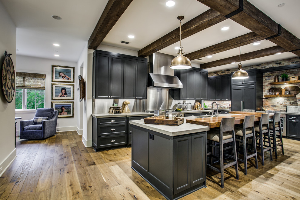 Kitchen - transitional l-shaped light wood floor and brown floor kitchen idea in Dallas with an undermount sink, recessed-panel cabinets, black cabinets, gray backsplash, an island and gray countertops