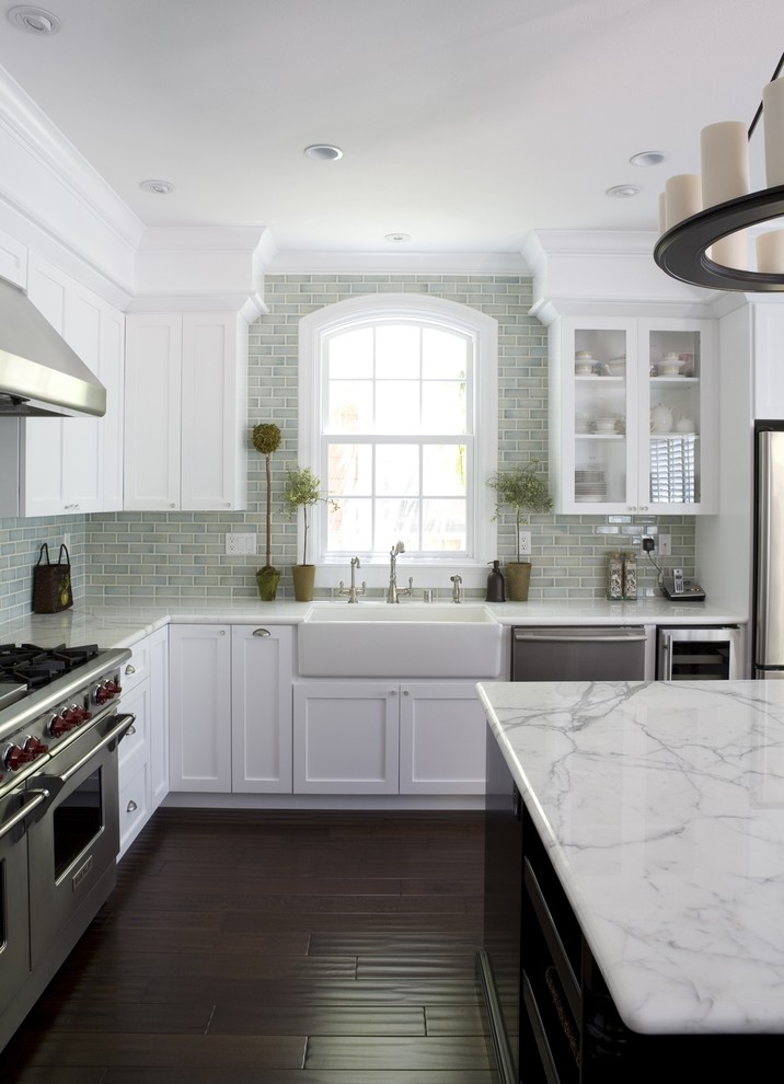Inspiration for a mid-sized timeless dark wood floor kitchen remodel in San Francisco with a farmhouse sink, stainless steel appliances, white countertops, shaker cabinets and white cabinets