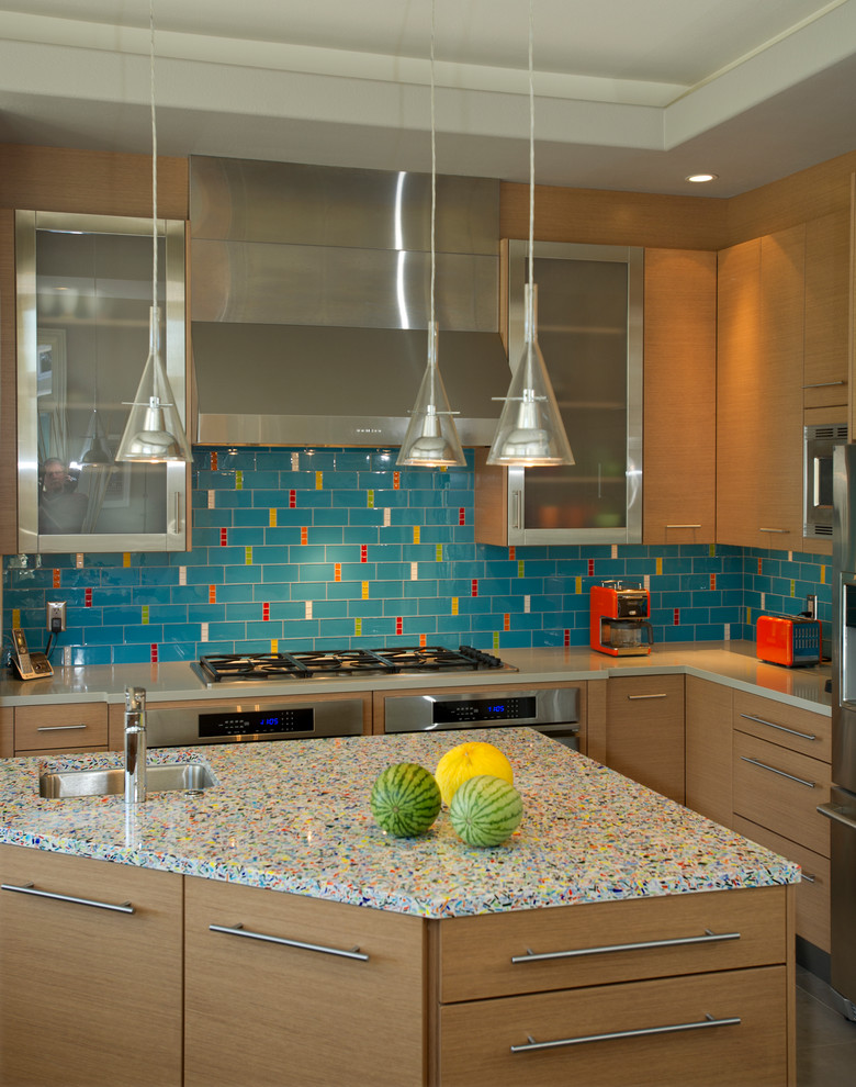 Inspiration for a mid-sized contemporary l-shaped porcelain tile enclosed kitchen remodel in San Francisco with recycled glass countertops, stainless steel appliances, flat-panel cabinets, medium tone wood cabinets, an undermount sink, multicolored backsplash, glass tile backsplash and an island