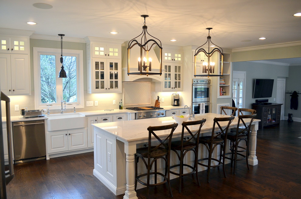 Example of a huge classic l-shaped dark wood floor open concept kitchen design in Nashville with a farmhouse sink, raised-panel cabinets, white cabinets, quartz countertops, white backsplash, ceramic backsplash, stainless steel appliances and an island