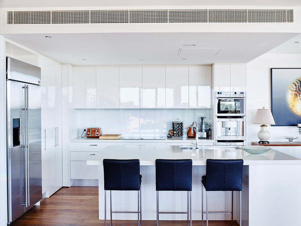 Kitchen - contemporary medium tone wood floor kitchen idea in Melbourne with an undermount sink, flat-panel cabinets, white cabinets, white backsplash, glass sheet backsplash, stainless steel appliances and an island