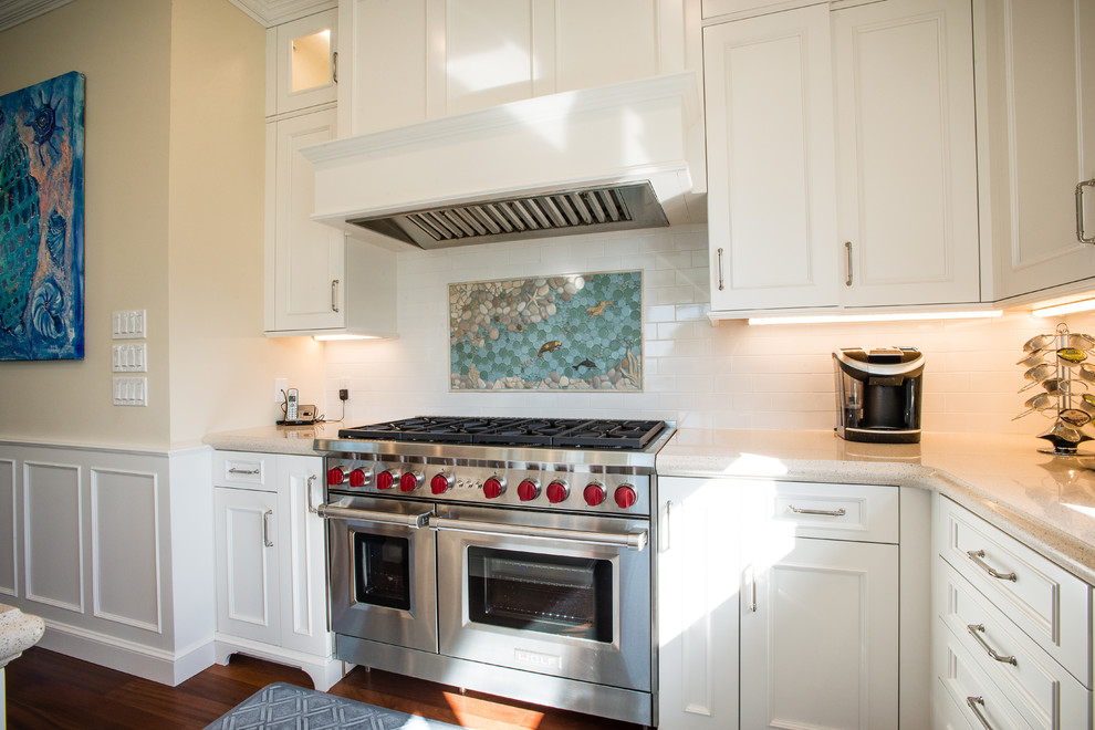 Large beach style l-shaped dark wood floor eat-in kitchen photo in Miami with a farmhouse sink, beaded inset cabinets, white cabinets, quartz countertops, white backsplash, subway tile backsplash, paneled appliances and an island