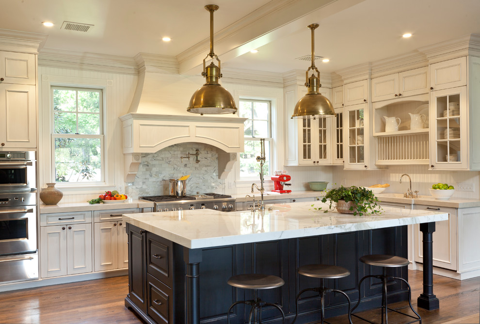 Eat-in kitchen - large traditional u-shaped dark wood floor eat-in kitchen idea in Santa Barbara with a farmhouse sink, recessed-panel cabinets, white cabinets, marble countertops, white backsplash, stainless steel appliances and an island