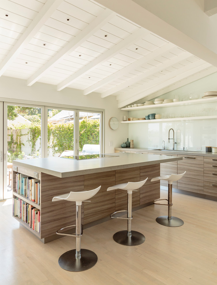 Trendy light wood floor kitchen photo in Santa Barbara with flat-panel cabinets, medium tone wood cabinets, white backsplash, glass sheet backsplash and an island