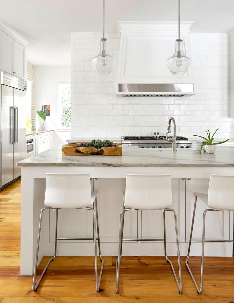 Farmhouse medium tone wood floor kitchen photo in Dallas with white cabinets, white backsplash, subway tile backsplash, stainless steel appliances and an island
