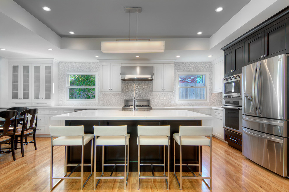 Large transitional l-shaped light wood floor open concept kitchen photo in San Francisco with a farmhouse sink, recessed-panel cabinets, white cabinets, quartz countertops, ceramic backsplash, stainless steel appliances, an island and white backsplash