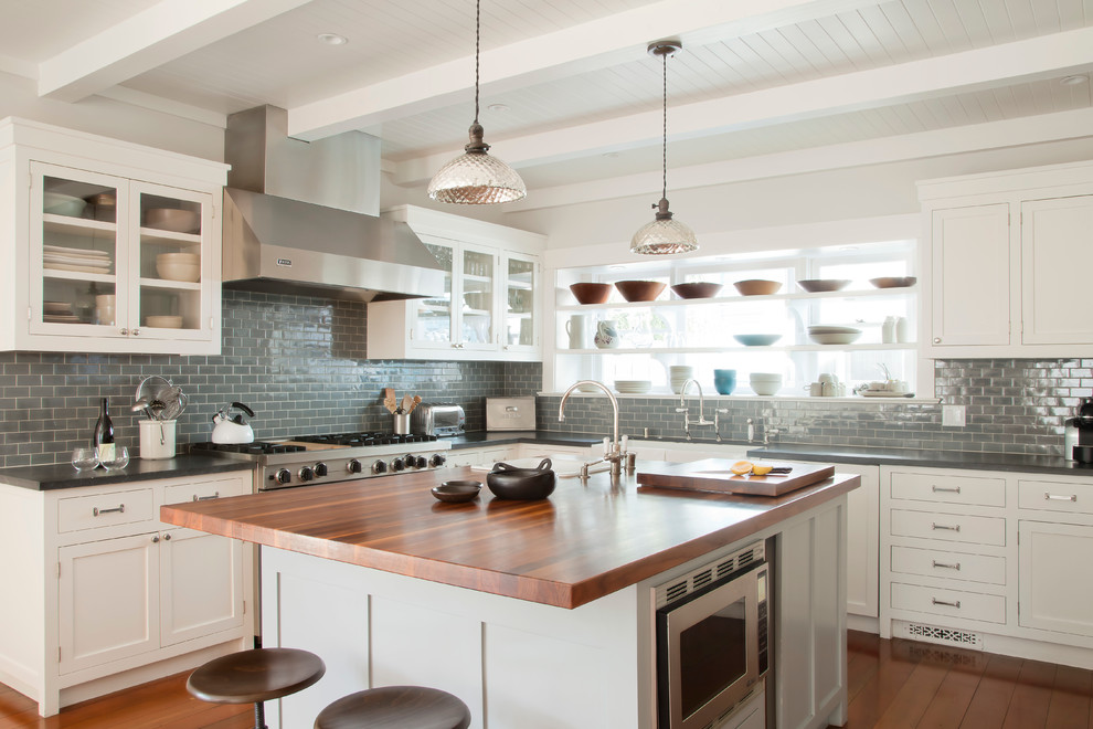 Kitchen - coastal kitchen idea in Los Angeles with glass-front cabinets, white cabinets, wood countertops, gray backsplash, subway tile backsplash and stainless steel appliances