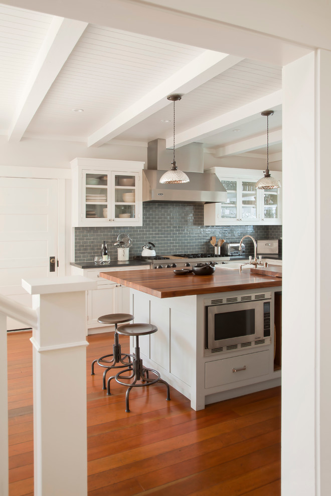 Inspiration for a coastal kitchen remodel in Los Angeles with glass-front cabinets, white cabinets, wood countertops, blue backsplash, subway tile backsplash and stainless steel appliances