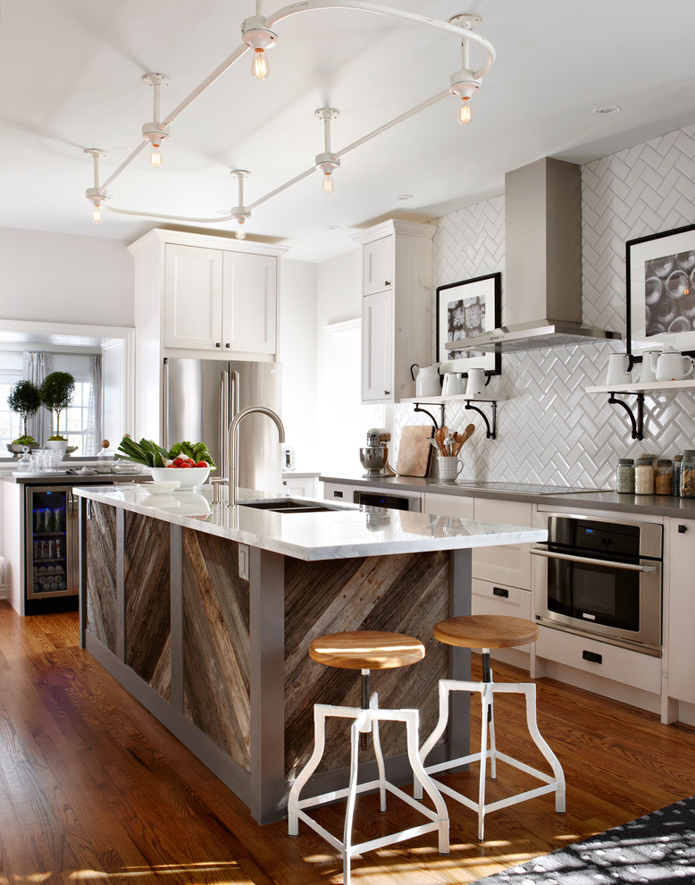 Elegant kitchen photo in Toronto with a double-bowl sink, shaker cabinets, white cabinets, white backsplash, subway tile backsplash and stainless steel appliances