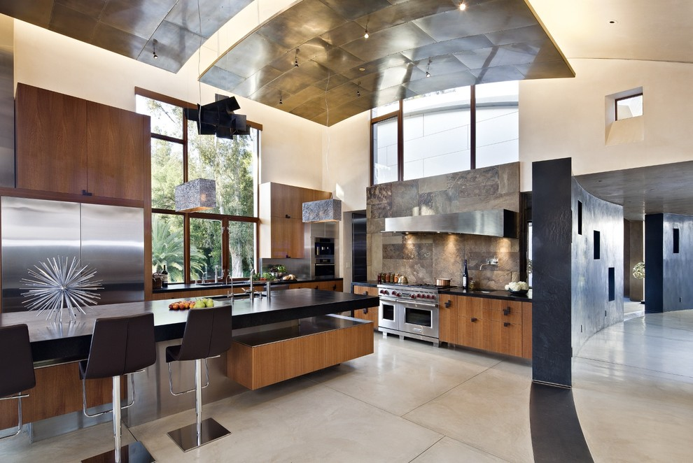 Large trendy l-shaped concrete floor and gray floor open concept kitchen photo in San Francisco with flat-panel cabinets, medium tone wood cabinets, soapstone countertops, brown backsplash, stainless steel appliances, slate backsplash, an undermount sink and an island