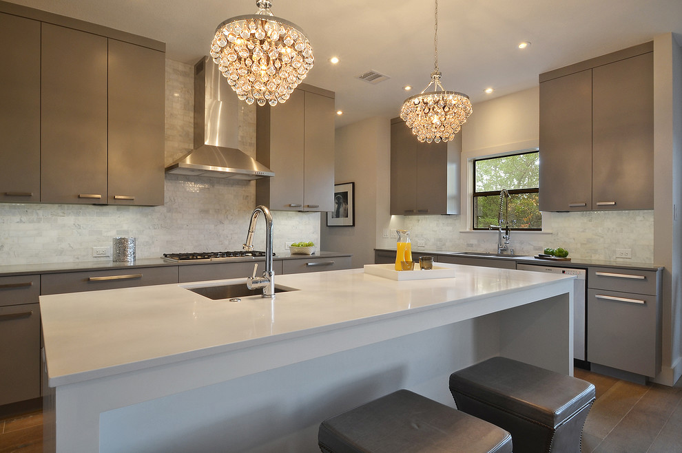 Inspiration for a transitional kitchen remodel in Austin with a single-bowl sink, flat-panel cabinets, gray cabinets, white backsplash, stone tile backsplash and stainless steel appliances