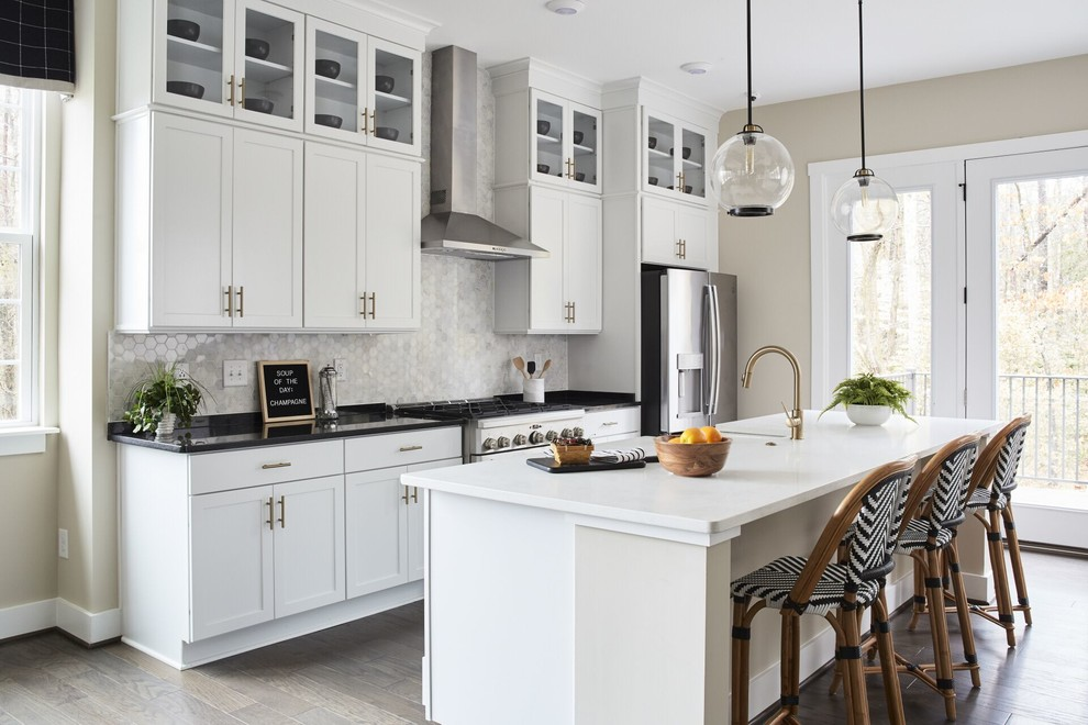 Example of a transitional galley medium tone wood floor and beige floor kitchen design in Other with a farmhouse sink, shaker cabinets, white cabinets, gray backsplash, stainless steel appliances, an island and black countertops